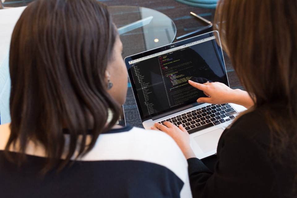 two people looking at code on a computer
